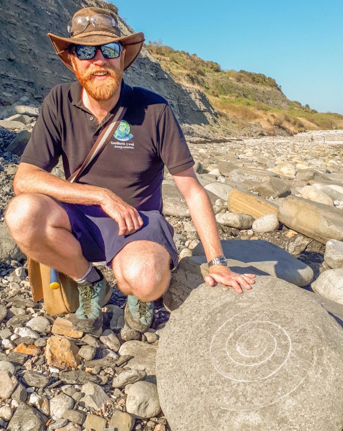 A photograph of James Cresswell with an ammonite fossil on Jurassic Coast at Lyme Regis
